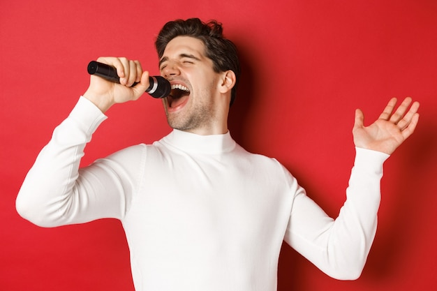 흰색 스웨터를 입은 잘생긴 남자가 노래를 부르고 마이크를 잡고 노래방에서 공연을 하고 빨간색 배경 위에 서 있습니다.
