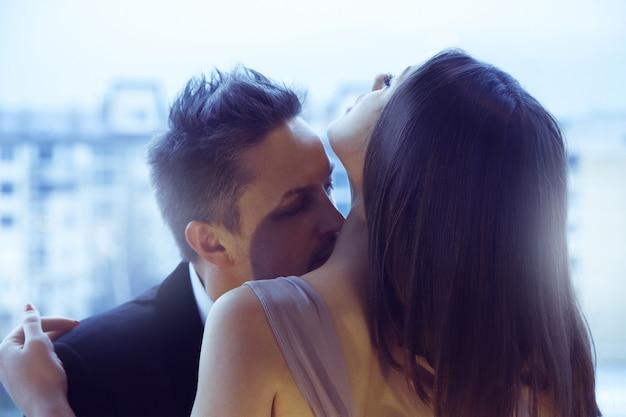 ハンサムな男は魅力的な女の子とイチャイチャしていて、首に彼女にキスします。情熱、愛、人間関係の概念