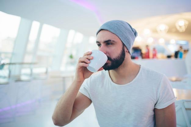 ハンサムな男はコーヒーカップを保持しています。