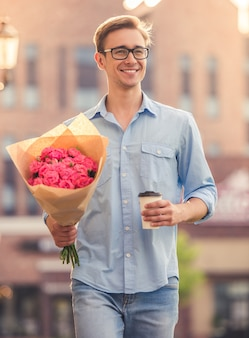 Handsome guy is holding flowers and a cup of coffee