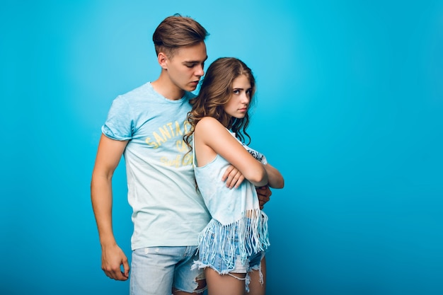 Handsome guy is hugging pretty girl with long hair on blue background in studio. she wears white t-shirt, shorts and looks offended.