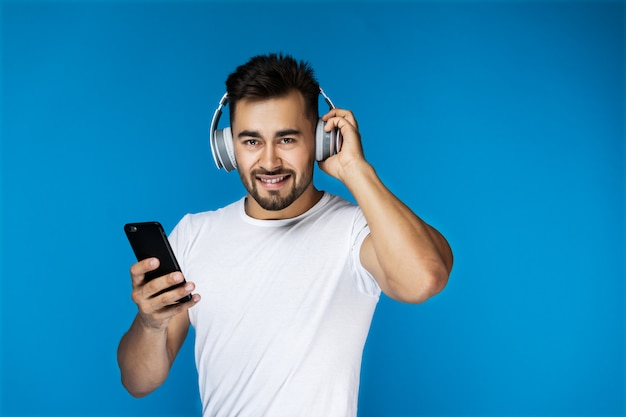 Handsome guy is listening music by headphones and holding cellphone in his arm