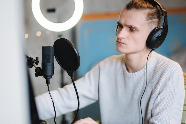 잘 생긴 남자가 마이크를 사용하여 팟 캐스트를 녹음하고 오디오 블로그 남자를위한 콘텐츠를 만들고 있습니다.