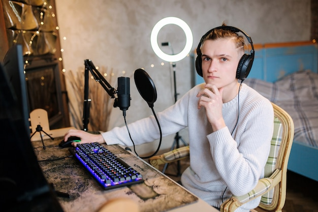 Handsome guy is recording podcast using microphone and creating content for audio blog man put on