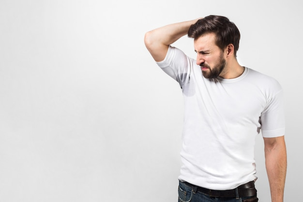 Handsome guy is sniffing his armpit. there is a big sweat spot and the guy doesn't like it at all and shrinking. he doesn't like the smell of it. isolated on white wall.
