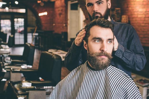 Красивый парень повернул голову вправо от парикмахера. парикмахер пытается получить хорошую прическу для своего клиента.