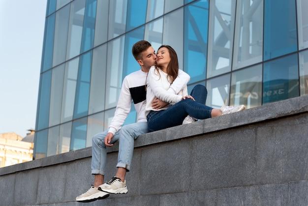 Красивый парень целует свою девушку. влюбленная пара отдыхает возле современного здания. свидание молодой пары в городе.