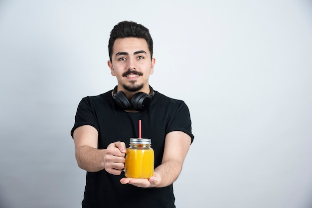 Handsome guy model in headphones showing glass cup with orange juice to camera .
