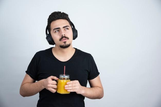 오렌지 주스와 유리 컵을 들고 헤드폰에 잘 생긴 남자 모델.