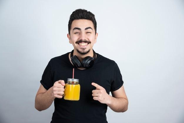 オレンジジュースとガラスのカップを保持しているヘッドフォンのハンサムな男モデル。