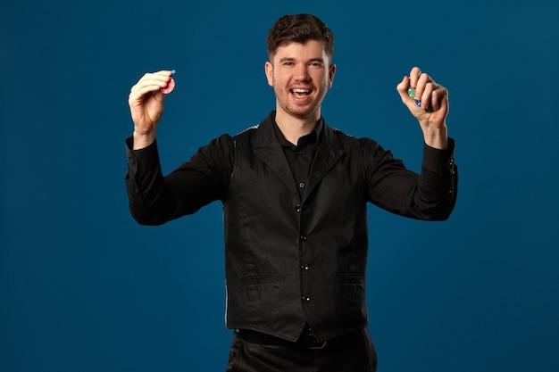 잘생긴 남자, 포커 초보자, 검은 조끼와 셔츠. 색색의 칩을 들고 기뻐하는 모습입니다. 블루 스튜디오 배경 포즈. 도박, 카지노. 확대.