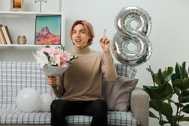 リビングルームのソファに座って花束を保持している幸せな女性の日にハンサムな男