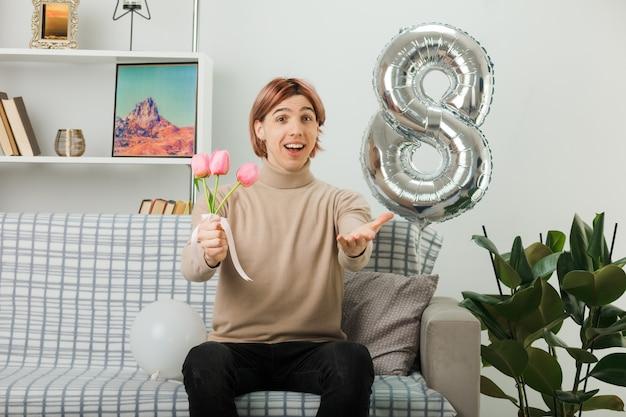 リビングルームのソファに座って花を保持している幸せな女性の日にハンサムな男