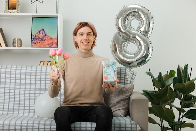 リビングルームのソファに座ってプレゼントと花を保持している幸せな女性の日にハンサムな男