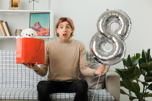 행복한 여성의 날에 잘생긴 남자가 거실 소파에 앉아 선물 가방을 들고 8번 풍선을 들고 있다