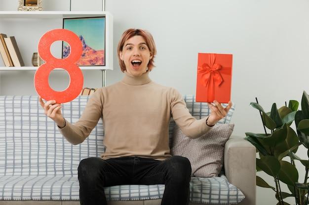 リビングルームのソファに座ってプレゼントと8番を保持している幸せな女性の日にハンサムな男