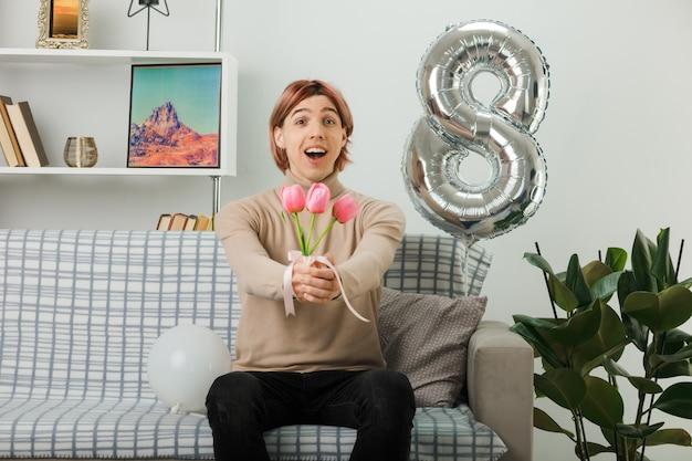 행복한 여성의 날에 잘생긴 남자는 거실에 있는 소파에 앉아 카메라에서 꽃을 들고 있다