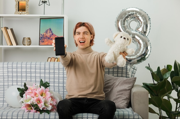 행복한 여성의 날에 잘생긴 남자가 거실에 있는 소파에 앉아 카메라로 테디베어를 들고 있다