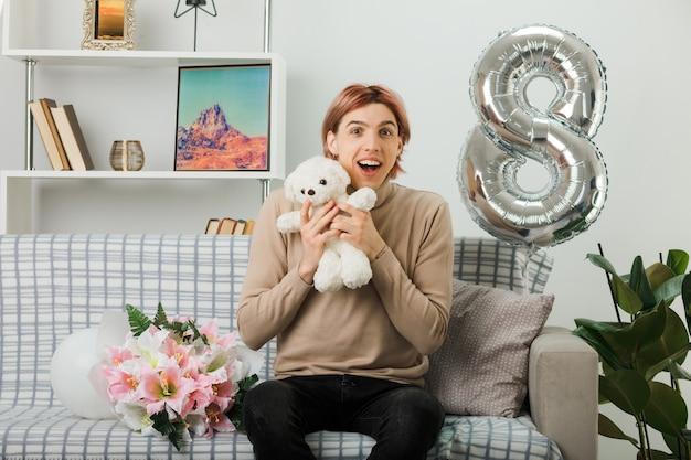 リビングルームのソファに座ってテディベアを保持している幸せな女性の日のハンサムな男