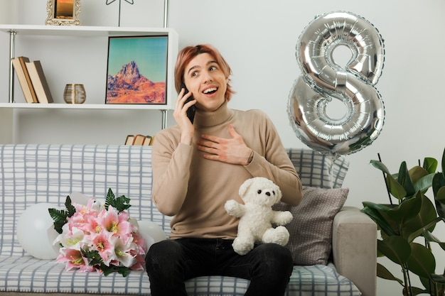 テディベアを保持している幸せな女性の日のハンサムな男は、リビングルームのソファに座って電話で話します