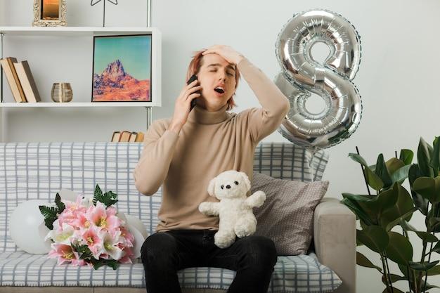 테디 베어를 들고 행복한 여성의 날에 잘 생긴 남자는 거실 소파에 앉아 전화로 말한다