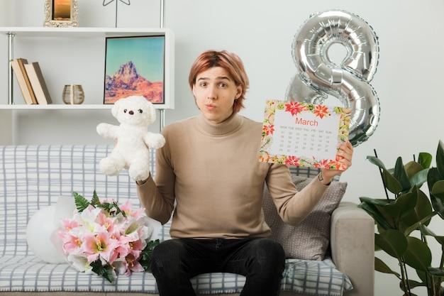 リビングルームのソファに座っているカレンダーとテディベアを保持している幸せな女性の日のハンサムな男