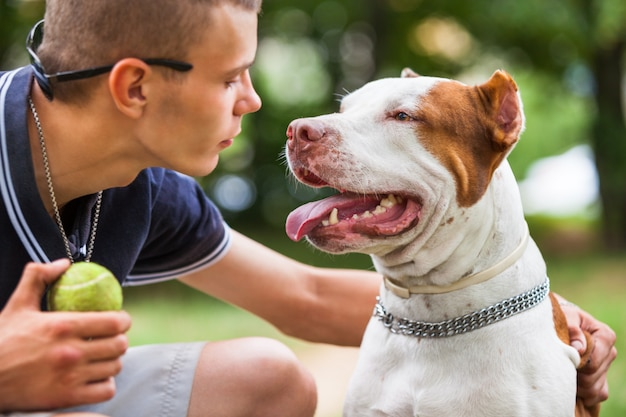 ハンサムな男が屋外の犬と遊ぶ。