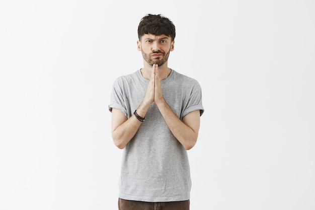 Handsome guy posing against the white wall praying