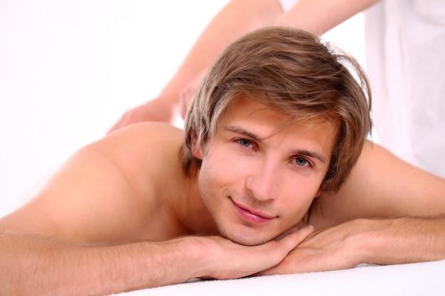 Красивый парень, расслабляющий на сеансе массажа