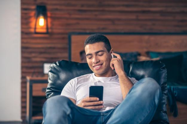 目を閉じて肘掛け椅子で、スマートフォンを手にヘッドホンで休んでいるハンサムな男。