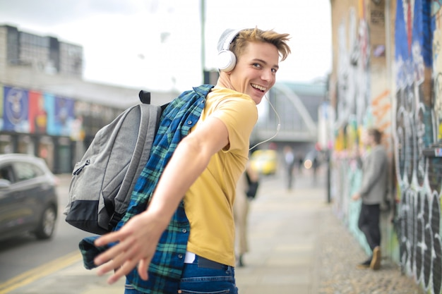 Handsome guy running in the street while listening music with headphones