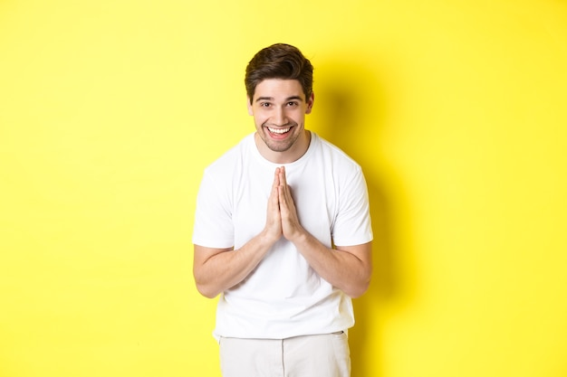 Bel ragazzo dicendo grazie, inchinandosi e tenendosi per mano in gesto di namaste, esprimere gratitudine, in piedi su sfondo giallo.