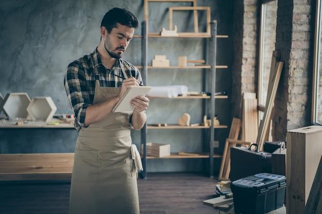 Красивый парень продавец администратор замечает заказ клиента подробности желания бумажный дневник ручка деревянный бизнес промышленность столярка гараж в помещении