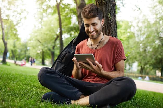 Красивый парень сидит в траве в парке, читает книгу на цифровом планшете, подключает wi-fi и просматривает социальные сети