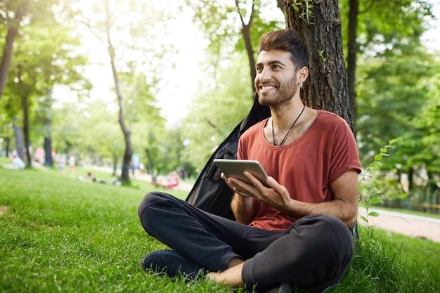 ハンサムな男が公園の芝生に座って、デジタルタブレットの本を読んで、wifiを接続し、ソーシャルメディアを見る
