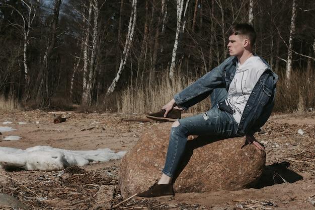 Красивый парень сидит на камне возле лесной полосы весной и смотрит на горизонт.