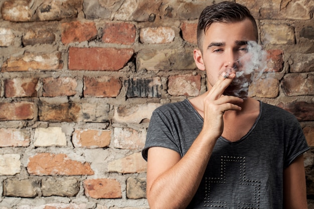 Handsome guy smoking near the wall