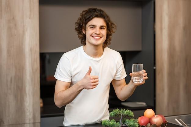 잘생긴 남자는 현대적인 주방에 머물며 아침 시간에 물 한 잔을 마신다