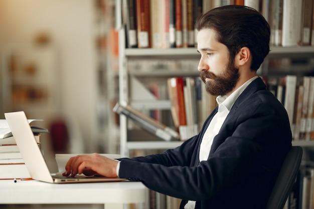 Красивый парень учиться в библиотеке