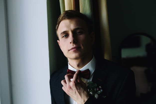 Handsome guy in suit posing holding bowtie
