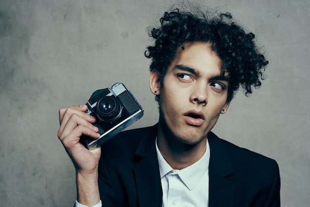 Handsome guy in a suit with a camera lessons curly hair emotions model
