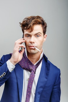 Handsome guy in a suit with a cigarette and talking on the phone