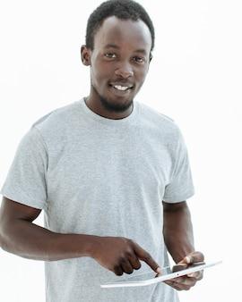 디지털 태블릿 화면에 두드리는 잘 생긴 남자. 흰색 배경에 고립