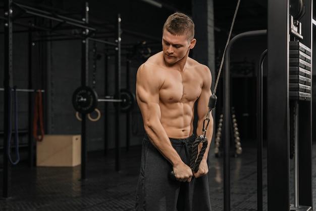 体育館のアスリートをポンプでくむジムで上腕三頭筋を訓練するハンサムな男。 crossfitトレーニング。