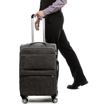 荷物を持って歩くハンサムな男。白いスペースに若い男の側面図