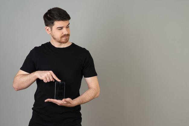 Красивый парень в повседневной одежде и держит телефон на сером. Premium Фотографии