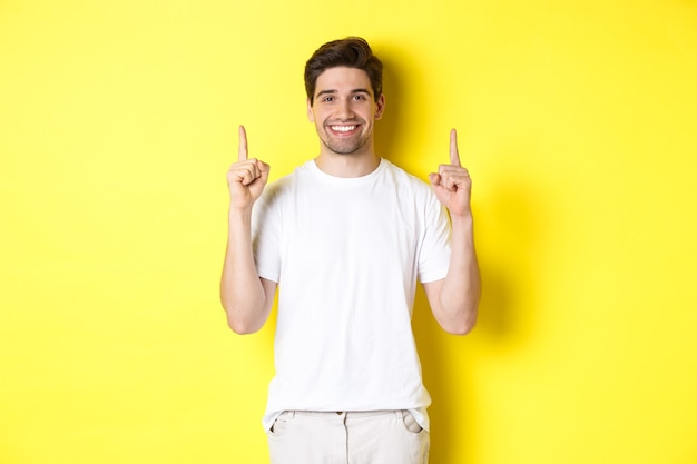 Handsome guy in white t-shirt pointing fingers up, showing shopping offers, standing over yellow background.