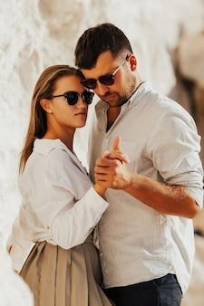 シャツにひげを生やしたハンサムな男は白いシャツを着た美しい少女の手を握ります