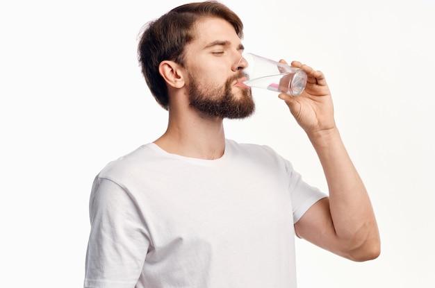 白いtシャツのクロップドビューモデルに水を一杯持っているハンサムな男。