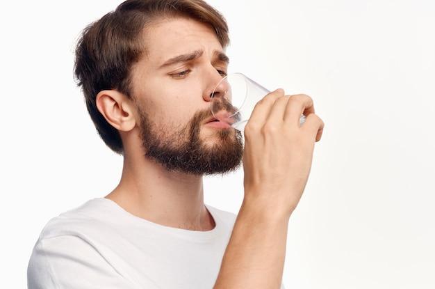 Красивый парень со стаканом воды на белой футболке обрезанный вид модель